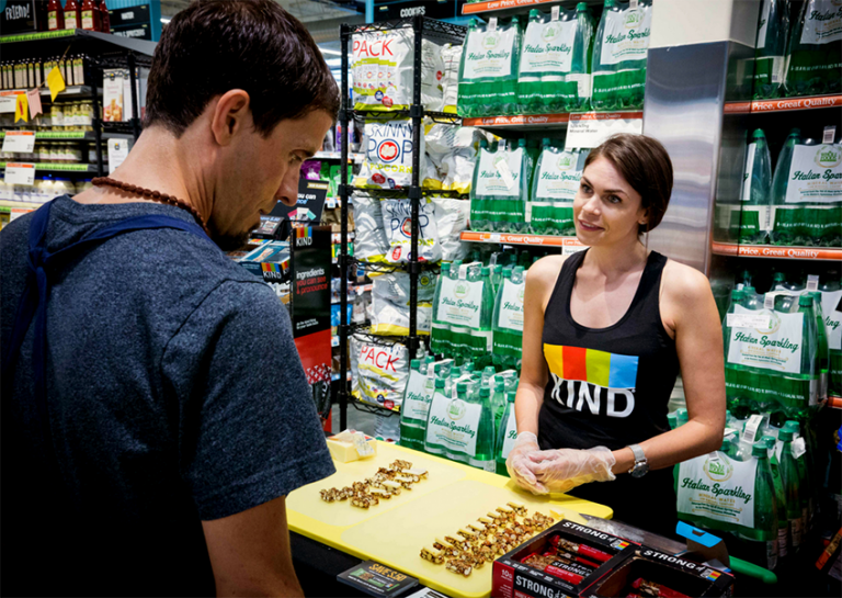 Woman offering kind bar samples to a customer