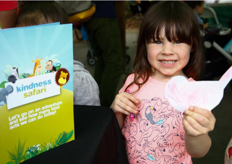 Little girl holding drawing of bird